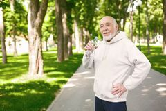 Senior man is having break, drinking water. Happy senior male runner is having break, drinking water while jogging in park Royalty Free Stock Photos