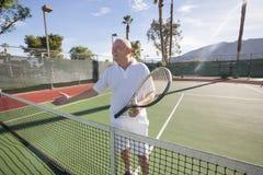 Happy senior male tennis player offering handshake on court stock image