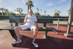 Happy senior male tennis player with water bottle sitting on bench at court Royalty Free Stock Photo