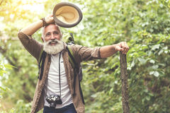 Happy senior male tourist hiking in forest Stock Photo