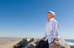 Happy Senior Man. Sitting on rocks on the beach stock photography