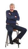 Happy senior man with arms crossed. Happy senior man laughs with arms crossed while sitting on stool.  He wears dark blue jeans and v-necked longsleeved shirt Royalty Free Stock Photos