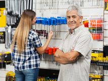 Happy Senior Man With Arms Crossed In Hardware Stock Photography