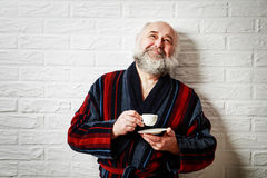 Happy Senior Man with Beard Drinking Coffee. Portrait of Happy Senior Man with Beard in Vintage Bathrobe Drinking Coffee and Dreaming. Mature Old Man with Coffee Royalty Free Stock Photos