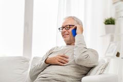Happy senior man calling on smartphone at home Stock Photos
