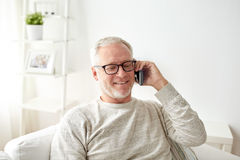Happy senior man calling on smartphone at home Stock Photography