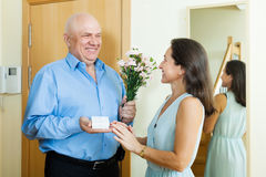 Happy senior man came to mature woman with present Royalty Free Stock Images