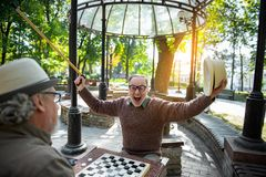 Happy senior man celebrating his victory in chequer game. Portrait of excited mature male pensioner winning his opponent in checkers. He is stretching arms up Stock Photo