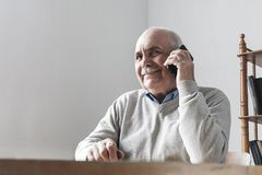 Happy senior man chatting on his mobile phone. Sitting at a table indoors listening to the conversation with a pleased smile stock photos