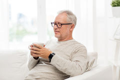 Happy senior man with cup of tea at home Stock Images