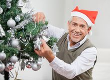 Happy Senior Man Decorating Christmas Tree Stock Photo