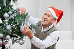 Happy Senior Man Decorating Christmas Tree Royalty Free Stock Photo
