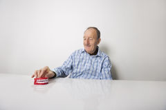 Happy senior man with dentures at table Stock Photo