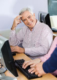 Happy Senior Man At Desk In Computer Class Royalty Free Stock Image
