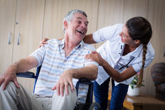 Happy senior man and doctor interacting in living room. Happy senior men and doctor interacting in living room at home Royalty Free Stock Images