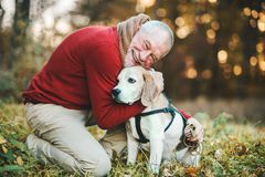 A senior man with a dog in an autumn nature at sunset. A happy senior man with a dog on a walk in an aun nature at sunset royalty free stock image