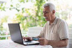 Happy Senior Man Doing Online Shopping Using Credit Card Outdoors in Garden. Or in Cafe stock photography
