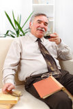 Happy senior man drinking coffee. Happy senior man in living room with books, drinking coffee Stock Photo