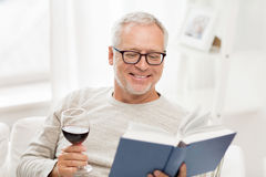 Happy senior man drinking wine and reading book Royalty Free Stock Image