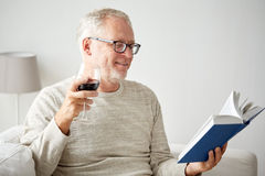 Happy senior man drinking wine and reading book Stock Photography