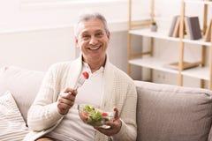 Happy senior man eating fresh vegetable salad stock photos
