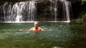 Happy Senior man enjoying the cool water of the waterfall. stock video
