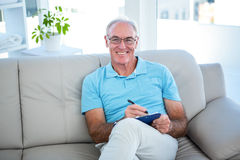Happy senior man in eyeglasses sitting on sofa with clipboard Royalty Free Stock Images