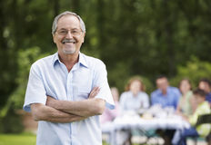 Happy Senior Man With Family In Background Stock Photo