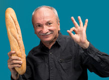 Happy senior man with fresh baguette Royalty Free Stock Photos