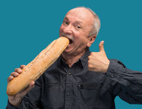 Happy senior man with fresh baguette Royalty Free Stock Images