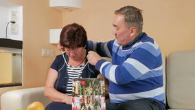 Happy senior man gives a woman's gift in package. He pulls out a pearl necklace and trying on her neck. Husband and wife stock footage