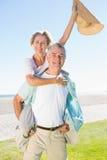 Happy senior man giving his partner a piggy back Stock Photos