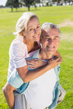 Happy senior man giving his partner a piggy back Stock Images