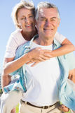 Happy senior man giving his partner a piggy back Stock Photo
