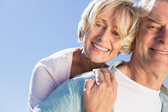 Happy senior man giving his partner a piggy back Royalty Free Stock Images