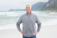 Happy senior man with hands on hips at beach Stock Image
