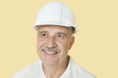 Happy senior man with hardhat over yellow background Royalty Free Stock Images