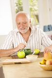 Happy senior man having tea in kitchen. Reading morning newspaper Royalty Free Stock Images