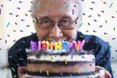 Happy senior man holding birthday cake royalty free stock images