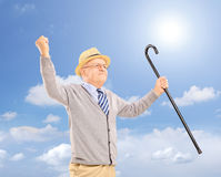 Happy senior man holding a cane and gesturing happiness outside stock photo