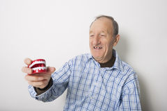 Happy senior man holding dentures against gray background Stock Photos