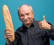 Happy senior man holding fresh baguette Stock Photography