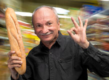 Happy senior man holding fresh baguette Stock Photos