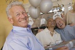 Happy Senior Man Holding Gift Stock Photos