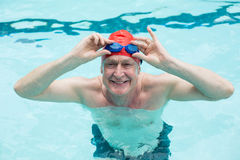 Happy senior man holding goggles in swimming pool Royalty Free Stock Photo