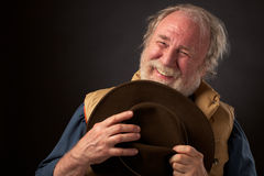 Happy senior man holding his hat. A cheerful healthy gray bearded senior man smiles and holds his brown slouch hat to his chest. He is wearing a sleeveless tan Stock Photos
