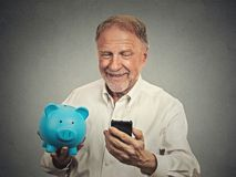 Happy senior man holding piggy bank looking at smart phone Stock Photo