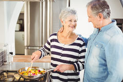 Happy senior man looking at wife cooking food Stock Images