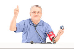 Happy senior man measuring blood pressure and giving a thumb up royalty free stock photography