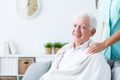Happy senior man at nursing home. Happy senior men covered with blanket at nursing home. Caregiver holding hands on his shoulders Stock Photography